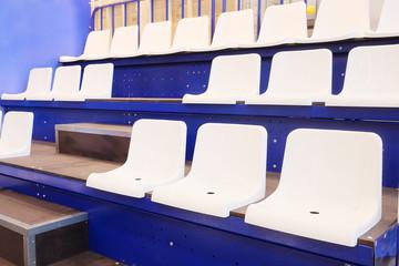 Empty white plastic chairs at the stadium