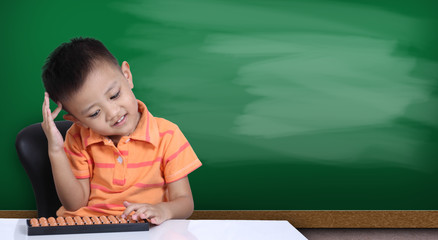 Little boy playing  abacus with green chalk board background