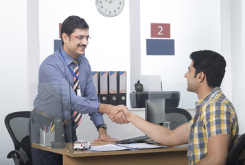 Bank executive shaking hand with the customer