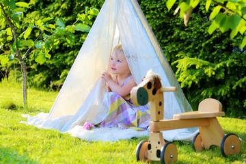 Preschooler girl playing in the garden hiding in tent