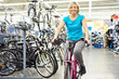 Attractive athletic woman testing bike in store