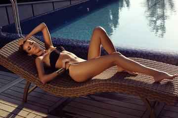 sexy girl in bikini relaxing beside a swimming pool