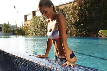 sexy blond in elegant bikini relaxing in swimming pool