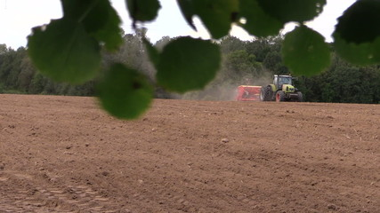 Tree branch with leaves move and tractor fertilize sow field