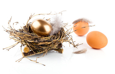 table decoration with easter eggs nest on plate, on white wooden
