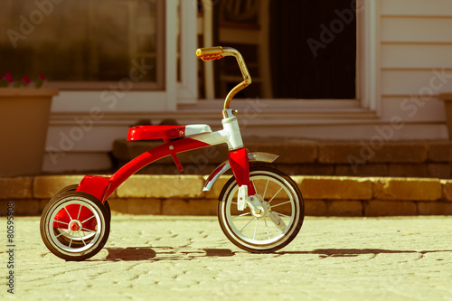 Poster Fietsen Child's rusted red tricycle standing ready