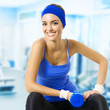 Happy woman doing fitness exercise, at gym