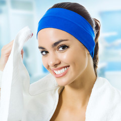Young woman in fitness wear with towel, at gym