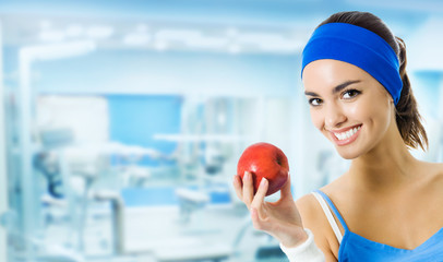 Young smiling woman with apple, at gym