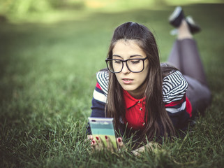 Beautiful young hipster girl using smart phone