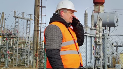 Worker talking on cell phone at power plant