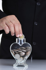 Businessman hand putting a coin into glass with heart shape