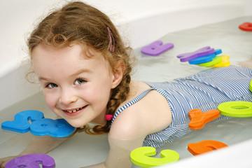 Little girl learning letters in the bath