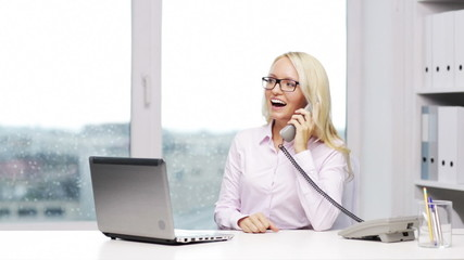 smiling businesswoman with laptop calling on phone