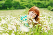 redhead woman   in field of daisies