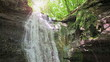 Forest waterfall in sunny summer day with sudden rain