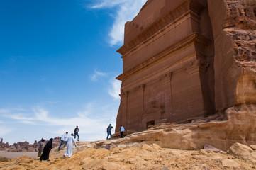 People entering a Nabatean tomb in Madaîn Saleh archeological s