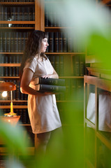 A pensive woman with the books through the green leaves