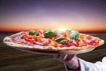 Frische Salami Pizza am Strand bei Sonnenuntergang serviert