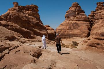 Saudian walking on top of rock formations, Saudi Arabia