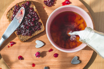 tea with pouring milk, homemade bread with blackcurrant jam