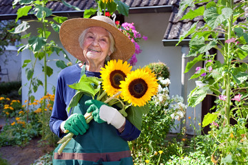 Happy Senior Woman Holding a Bouquet of Sunflowers.