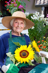 Old Woman in Gardening Outfit Holding Sunflowers.