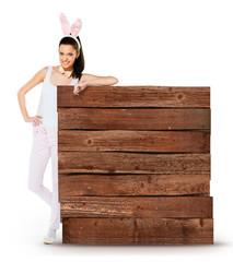Cute woman with bunny ears with a wooden blank sign isolated