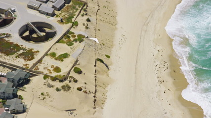 Aerial view of hang glider flying over beach