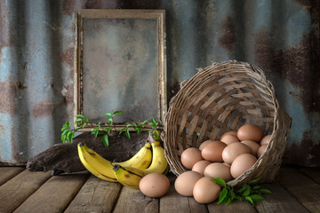 Still life with eggs, banana and old photo frame on wood table w