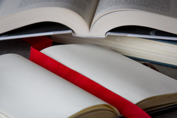 Open books on table with red ribbon