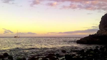 Timelapse of wild stone beach on coast of ocean at sunset