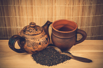 old clay teapot and black leaf tea
