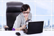 Businesswoman using magnifying glass on laptop