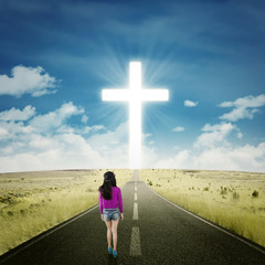 Girl walking on the road with a cross