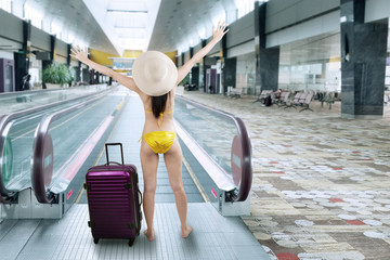 Happy woman wearing bikini in airport hall 1