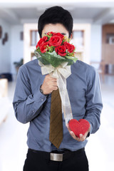 Man holding flowers and gift
