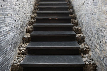 marble staircase with stone wall