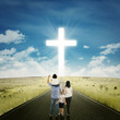 Parents and kids on the road with a cross
