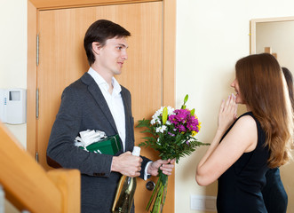 Young smiling man giving gifts to cute woman at home