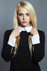 Young blond sexy woman in black schoolgirl dress