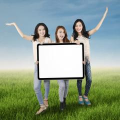 Teenage girls with billboard on meadow