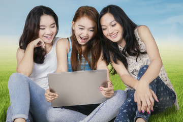 Three college students with laptop at field