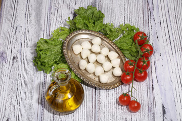Mozzarella, leaves of green salad, tomatoes and olive oil