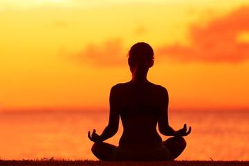 Wellness woman doing zen yoga meditation on beach
