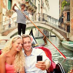 Selfie couple using smartphone in Venice gondola