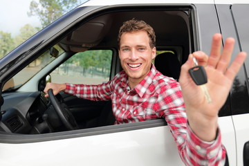 Happy driving man showing new car keys or rental