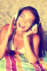 Woman listening to music with headphones at beach