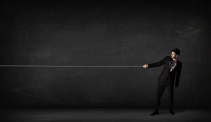 Businessman pulling rope on grey background