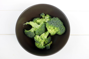 Broccoli in a Dark Brown Bowl on a White Wooden Background